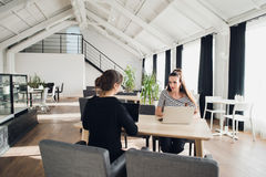 Female business team having a meeting together to discuss paperwork sitting at a table having a discussion. Two. Businesswomen sitting at a table with laptops Royalty Free Stock Photos