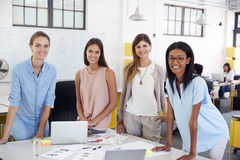 Female business team stand at office desk looking to camera Royalty Free Stock Images