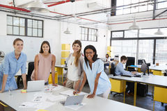 Female business team stand at office desk looking to camera Stock Photos