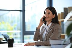Free Female Business Trainer Talking On Phone While Working With Laptop Royalty Free Stock Image - 162421476