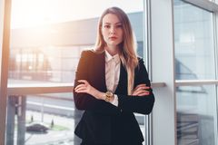 Female business traveler standing against window with airport arrival corridor view.  Stock Photo