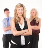 Female Business woman with arms Folded. And her team in the background Stock Photo