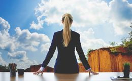 Female business woman looking out the windows sky mountain. Female business woman is looking out the windows sky mountain royalty free stock photos