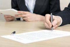 Female businessperson signs contract Stock Image