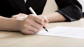 Female businessperson signs contract. Close up of female hand signing formal paper on the office table. The business counterpart on the background Stock Photo