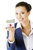 Female businesswoman holding and protecting house. Stock Photos