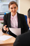 Female Businesswoman Interviewing Male Job Candidate Stock Photo