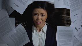 Female businesswoman overwhelmed with paperwork, hiding face in horror, closeup