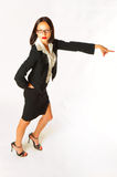 Female businesswoman pointing. Attractive young businesswoman with smart suit and glasses pointing; white studio background Stock Photos