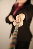 Female businesswoman pulling rope. Female businesswoman pulling a colorful rope Royalty Free Stock Photo