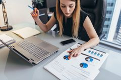 Female businesswoman readind financial report analyzing statistics pointing at pie chart working at her desk.  Stock Photo