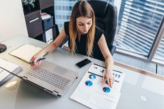 Female businesswoman readind financial report analyzing statistics pointing at pie chart working at her desk royalty free stock images