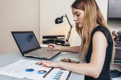 Female businesswoman readind financial report analyzing statistics pointing at pie chart working at her desk.  Royalty Free Stock Photos
