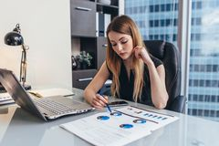 Female businesswoman readind financial report analyzing statistics pointing at pie chart working at her desk stock images