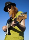 Female busker with guitar. Stylish female musician with red hairs wearer in black hat and green shirt plays on the guitar. Deep blue sky on the background. Focus Stock Images