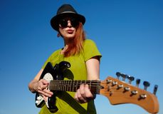 Female busker with guitar. Stylish female musician with red hairs wearer in black hat and green shirt plays on the guitar. Deep blue sky on the background. Focus Stock Photo