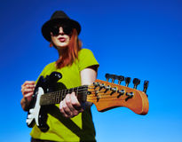 Female busker with guitar. Stylish female musician with red hairs wearer in black hat and green shirt plays on the guitar. Deep blue sky on the background. Focus Stock Image