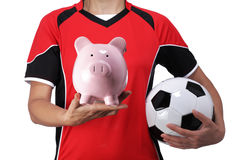 Female bust in Football Uniform holding a piggy bank Royalty Free Stock Photography