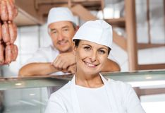 Female Butcher With Colleague At Shop Royalty Free Stock Photography