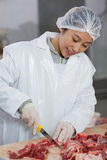Female butcher cutting meat at meat factory Stock Photo