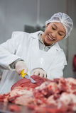 Female butcher cutting meat at meat factory Royalty Free Stock Photos