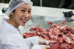 Female butcher cutting meat at meat factory Royalty Free Stock Photography