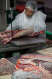Female butcher cutting raw meat on a band saw machine Stock Photo