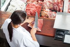 Female Butcher Cutting Red Meat Royalty Free Stock Image