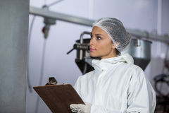 Female butcher maintaining records on clipboard. At meat factory Royalty Free Stock Photo