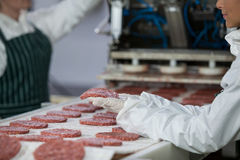 Female butcher processing hamburger patty. At meat factory Royalty Free Stock Images
