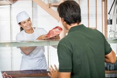Female Butcher Selling Fresh Meat To Customer Royalty Free Stock Photos