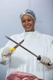 Female butcher sharpening her knife Stock Photos