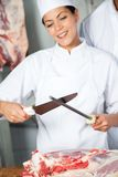 Female Butcher Sharpening Knife Stock Image
