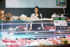 Female butcher with wurst and bologna in meat store counter Stock Image