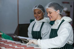 Female butchers maintaining records on clipboard Royalty Free Stock Images