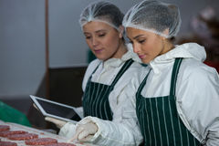 Female butchers maintaining records over digital tablet Royalty Free Stock Photography