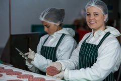 Female butchers maintaining records over digital tablet Royalty Free Stock Photo