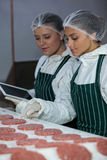 Female butchers maintaining records over digital tablet Stock Photo