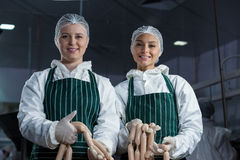 Female butchers processing sausages Royalty Free Stock Photos