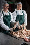 Female butchers processing sausages Royalty Free Stock Photo