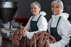 Female butchers processing sausages Royalty Free Stock Images