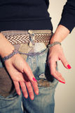 Female buttocks with handcuffs. Female buttocks in jeans with handcuffs from steel chain Royalty Free Stock Photo