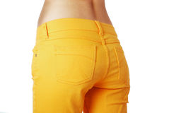 Female buttocks in loose jeans, side view. Slender hips are wearing an orange jeans loose-fitting Royalty Free Stock Image