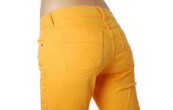 Female buttocks in loose jeans, side view. Slender hips are wearing an orange jeans loose-fitting Royalty Free Stock Photography