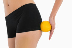 Female buttocks with orange rolling on it Royalty Free Stock Photography