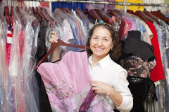 Female buyer chooses evening dress. In clothing store Stock Photo