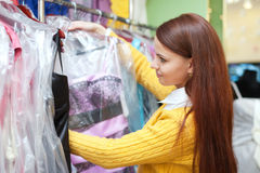 Female buyer chooses evening dress at  store Royalty Free Stock Image