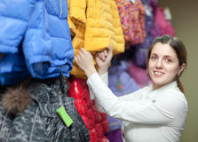 Female buyer chooses the winter jacket. In the store Royalty Free Stock Photography