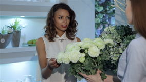 Female buyer examines the bouquet of roses. Pretty female buyer examining beautiful bouquet of white roses at the flower shop. Young caucasian woman touching stock footage