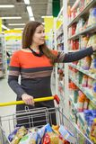Female buyer gets pack with cereal from shelf of cash-and-carry store Stock Images